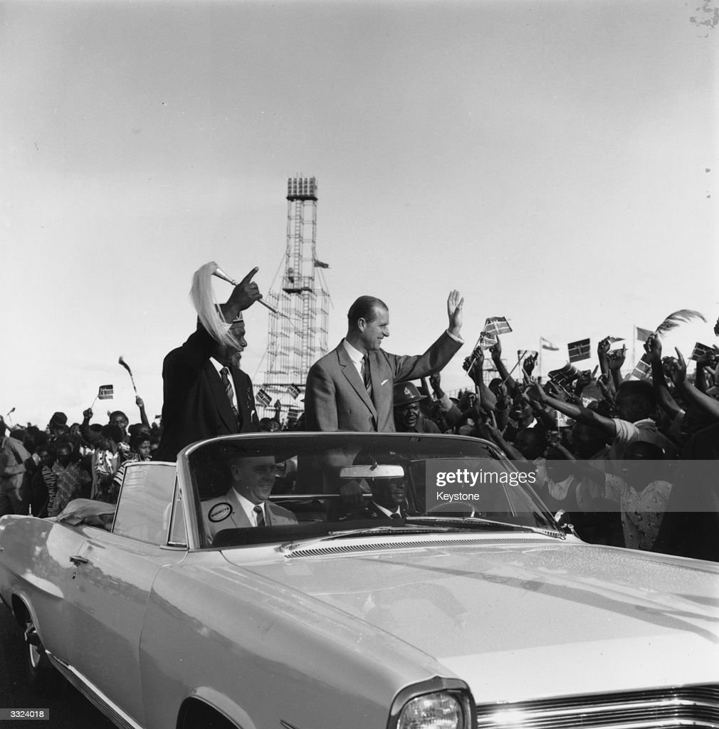 Kenyan Prime Minister Jomo Kenyatta (c 1889 - 1978) and the Duke of Edinburgh drive through cheering crowds in Nairobi during the Independence celebration
