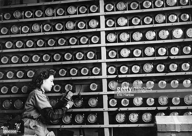 A woman checking alarm clocks at S Smith and Sons clock factory in Cricklewood London