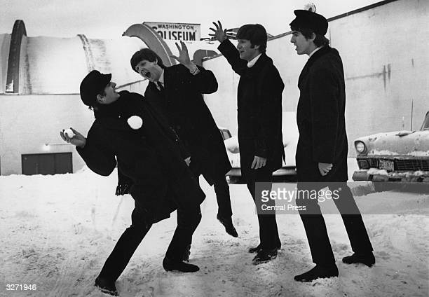 The Beatles soon after their arrival in Washington USA playing in the snow outside the Coliseum where they were scheduled to perform before a sellout...