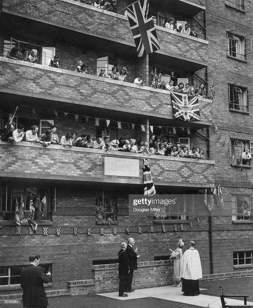 Queen Elizabeth (1900 - 2002) unveiling a plaque to commemorate the opening of Malcolmson House, a new block of flats on the Tachbrook Estate in Westminster.