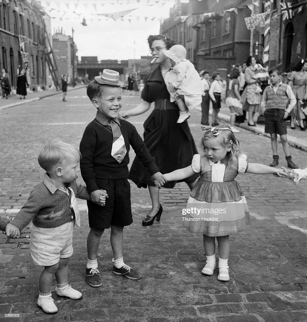 Children dancing at a street party at Morpeth Street, in London's East End, to celebrate the coronation of Queen Elizabeth II. The small boy in white shorts is Reggie Lewis, and the boy in dark shorts with a tie is Ted Lewis. Original Publication: Picture Post - 6542 - Cockneys' Own Party - pub. 1953
