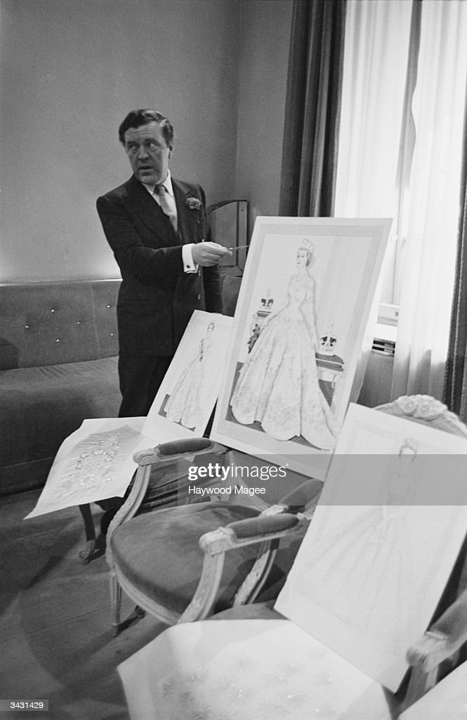 Couturier Norman Hartnell (1901 - 1978) with his design for the Queen's coronation dress.