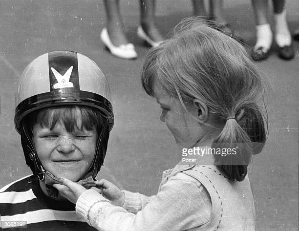 A girl helps to put on her friends safety helmet during a pedal car grand prix