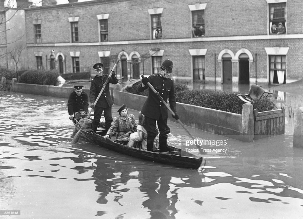 Policemen in a rowing boat rescue inhabitants of Spring Lane, Clapton, London, where flood waters have reached alarming heights after the River Lea burst its banks.