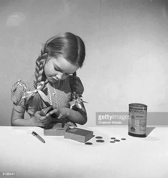 A little girl with pigtails empties her money box and purse