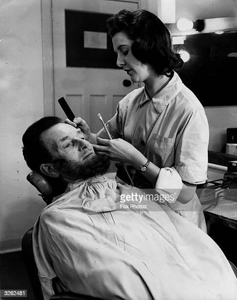 Instructor W T Tyler having a false beard applied by makeup trainee