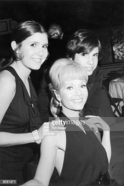American actor Debbie Reynolds sits and smiles with her children actor Carrie Fisher and Todd Fisher as they attend the opening night party for the...