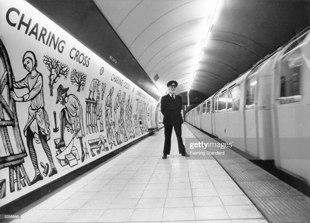 Making a change from the usual graffiti, the new murals on Charing Cross station are shown off by London Transport Manager Denis Hicks.