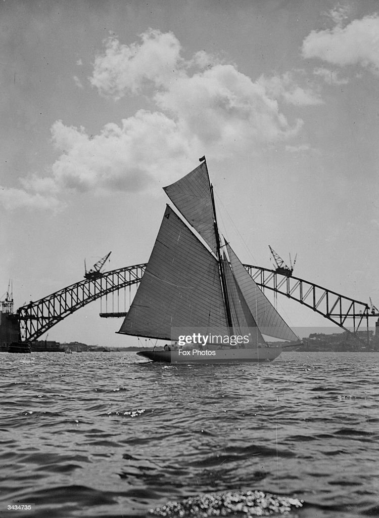 Yachting in Sydney harbour.The Sydney Harbour Bridge is being constructed in the background.