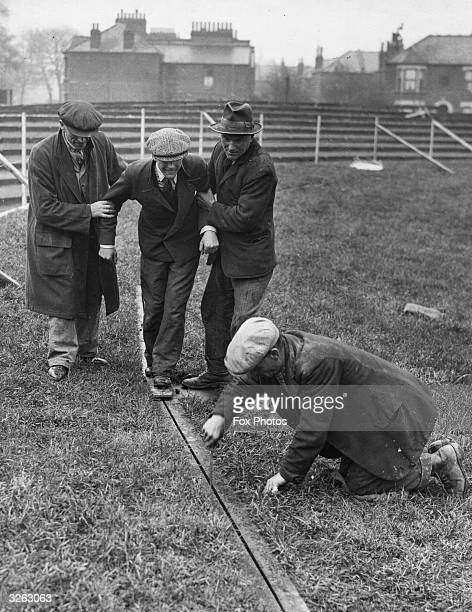 A member of the groundstaff being supported as he tries out the rail on which the hare will travel during the construction of a new dog racing track...