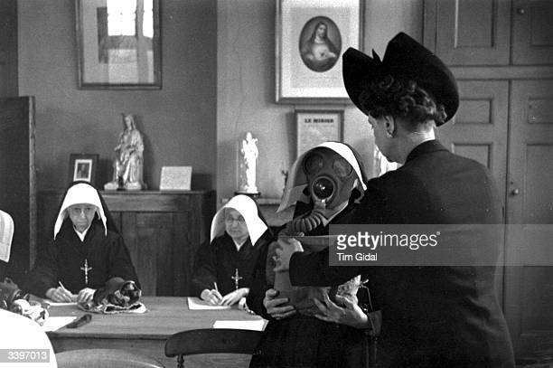 A volunteer with the Women's Voluntary Service for Civil Defence trains nuns how to use gas masks as Britain prepares for the possibility of a major...