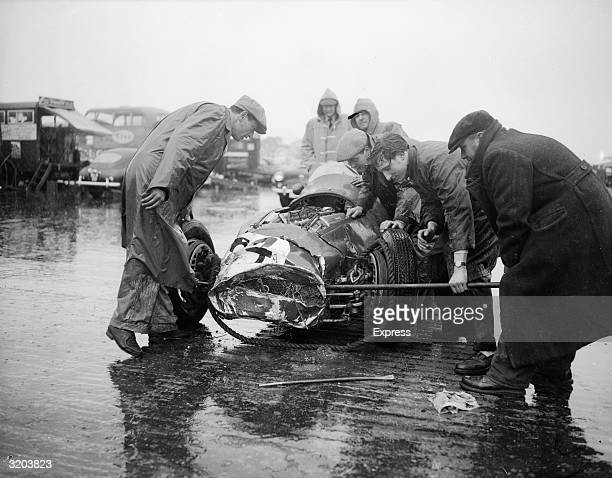 Mechanics use a crowbar in an attempt to straighten out the bodywork of the Marquis de Portago's wrecked Ferrari which they have just dragged off the...