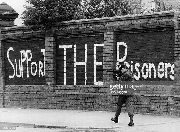 A British soldier looking out for snipers as he patrols the Falls Road in Belfast The graffiti in the background is in support of Bobby Sands and his...