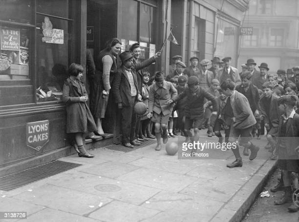 Boys playing football along the pavement watched by a crowd in 'Little Italy' Clerkenwell London in anticipation of an International match between...