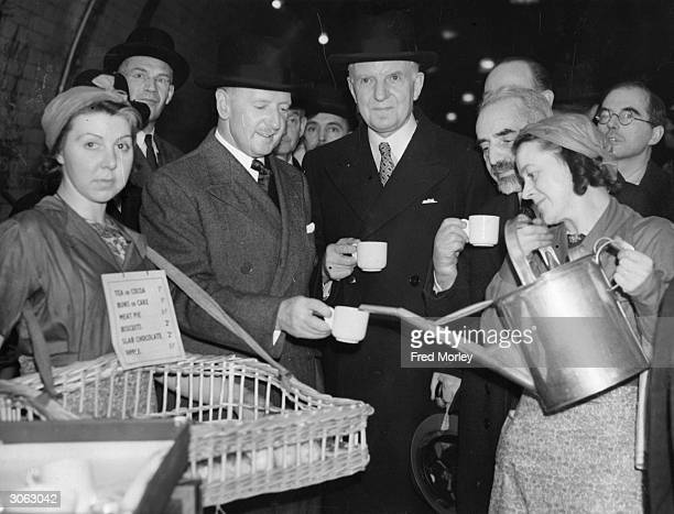 Sir George Wilkinson the Lord Mayor of London and the Minister for Food Lord Woolton enjoying a cup of tea in an underground station air raid shelter