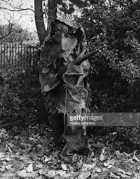 A young gunner in the London homeguard demonstrates camouflage techniques With his face and hands blackened he uses old wallpaper to disguise himself...