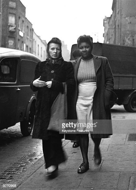Two women chatting as they walk down Cable Street in Stepneyeast London