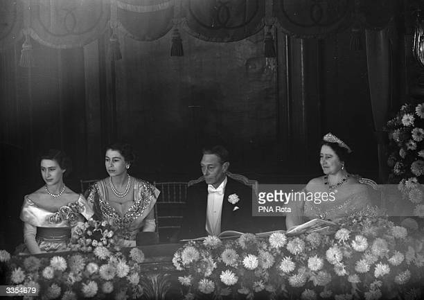 King George VI watching the Royal Command Performance at the London Palladium with Queen Elizabeth and their daughters Princesses Margaret Rose and...