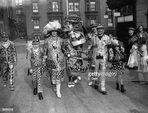 Pearly Kings and Queens carrying gifts of fruit and bread to St Mary Magdalene Church in London for the Costers Harvest Festival Service