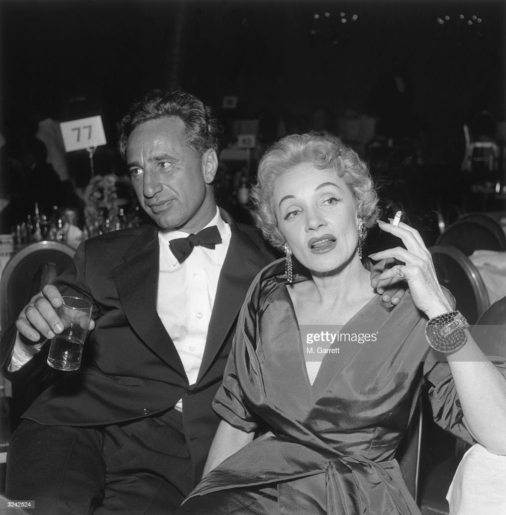 Turkish-born film director Elia Kazan (1909 - 2003) and German-born actor Marlene Dietrich (1901 - 1992) sit together at the premiere reception for director George Cukor's film, 'A Star is Born,' Hollywood, California. Kazan holds a drink, and Dietrich holds a cigarette.
