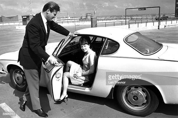 English film actor Roger Moore opening the door of his Volvo for Isabelle McMillan in a scene from the television series 'The Saint'