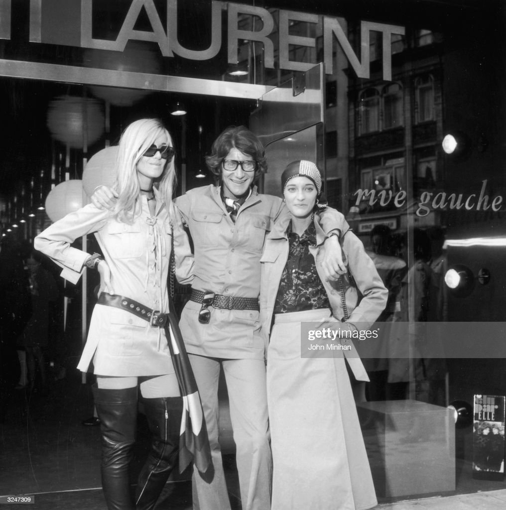 French designer Yves SaintLaurent poses with two fashion models Betty Catroux and Loulou de la Falaise outside Rive Gauche his new London boutique