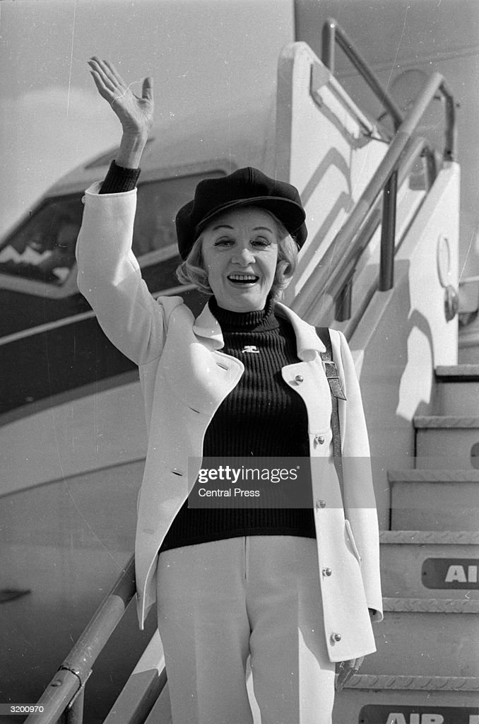 Sixty seven year old <a gi-track='captionPersonalityLinkClicked' href=/galleries/search?phrase=Marlene+Dietrich&family=editorial&specificpeople=70018 ng-click='$event.stopPropagation()'>Marlene Dietrich</a> (1901 - 1992) waving from the steps of a plane at Heathrow Airport, London. She is visitng England to appear in a Midnight Charity Performance in aid of the mentally handicapped.