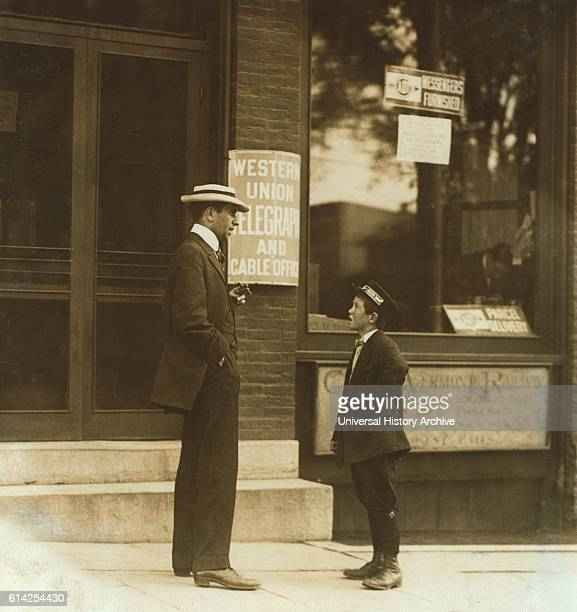 13yearold Western Union Messenger Boy Talking to Man outside Office Usually Works from Noon to 1030pm Burlington Vermont USA circa 1910