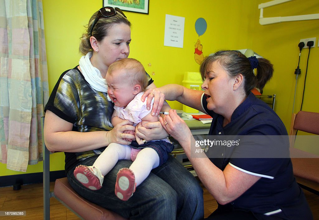 14-month-old Amelia Down sits on the lap of her mother Helen (L) as she receives the combined Measles Mumps and Rubella (MMR) vaccination at an MMR drop-in clinic at Neath Port Talbot Hospital near Swansea in south Wales on April 20, 2013. Public health officials said on April 19 they were investigating the first suspected death from measles in Britain in five years, after an outbreak blamed on a campaign against vaccinations. More than 800 people have contracted the highly contagious disease in Wales in the past six months, centred around the southern city of Swansea. Marion Lyons, director of health protection for Wales, said it had now been confirmed that a 25-year-old man from Swansea who died on April 18 had measles, a full postmortem will be conducted to determine cause of death.