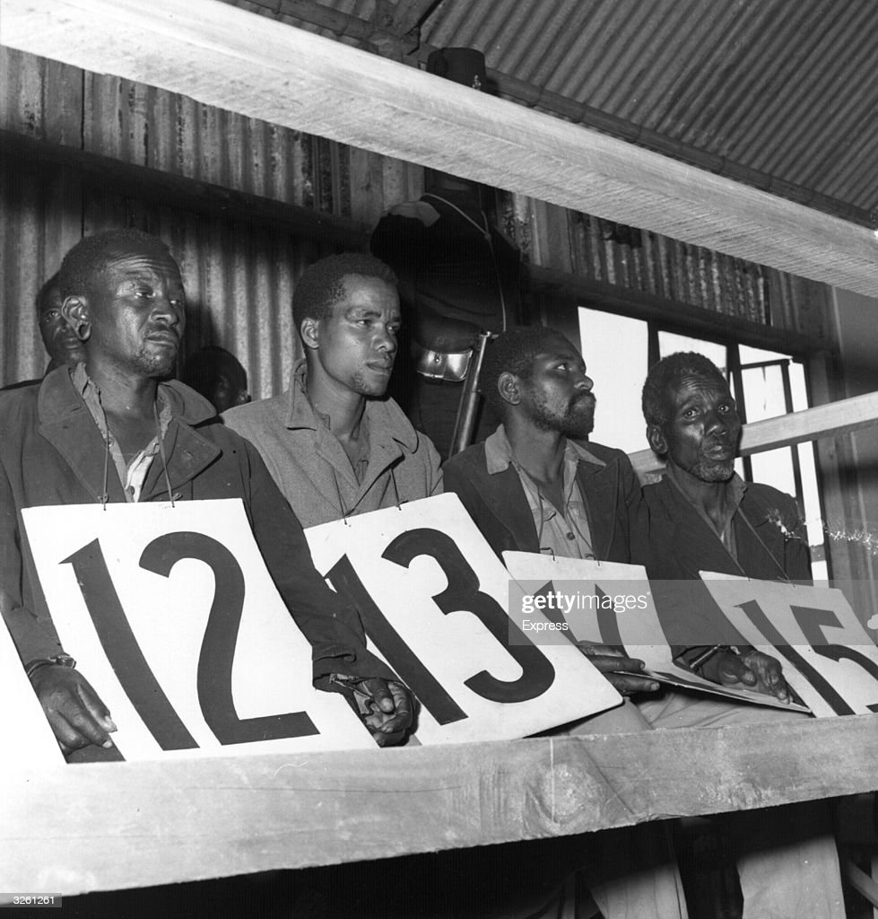 Suspected members of the Mau Mau, accused of murder and on trial. They are sitting in a shed, holding large identifying numbers on their laps.