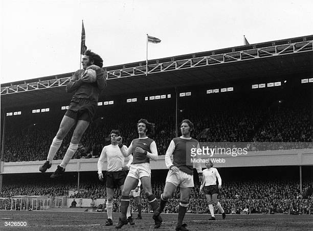 Tottenham Hotspur goalkeeper Pat Jennings gathers the ball in the air ahead of Arsenal attackers Alan Ball and Jeff Blockley and watched by Spurs...