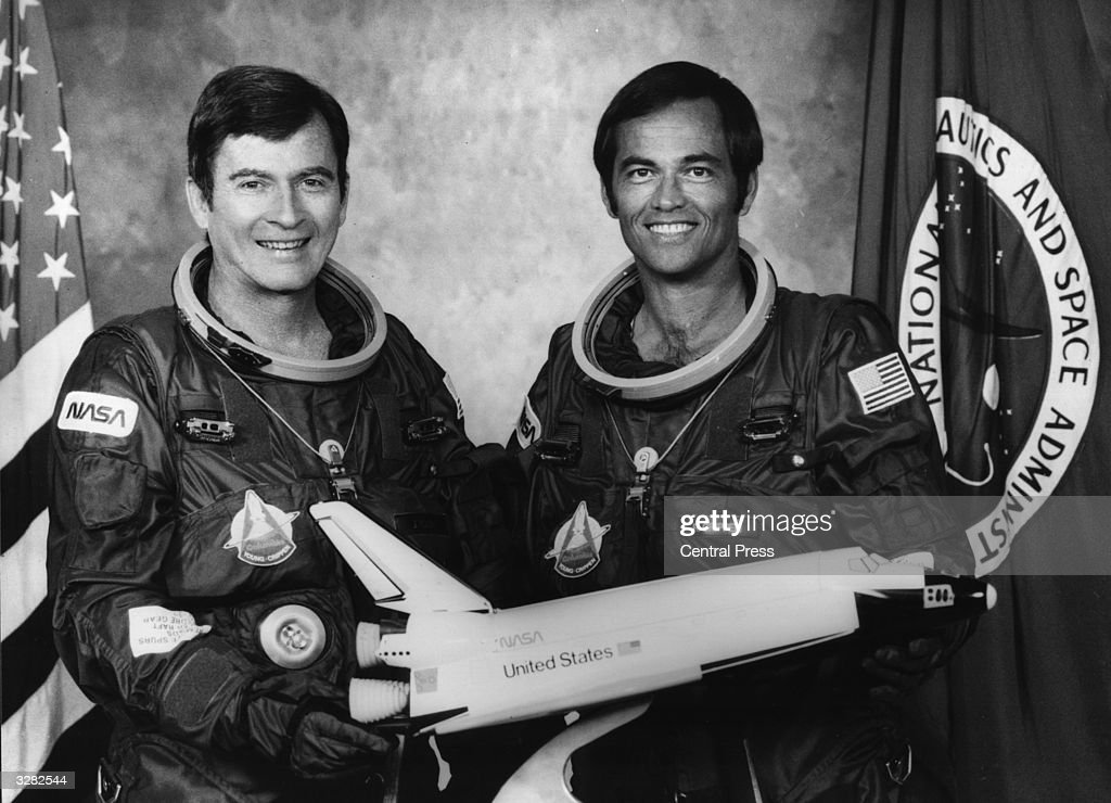 The prime crew commander, John Young and the pilot, Robert Crippen, with a model of the Space Shuttle orbiter Columbia.