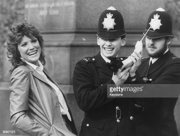 British actress Suzanne Danielle sharing a joke with two policemen while they examine one of the newly legal mobile phones