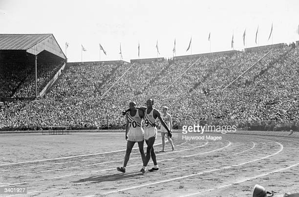 American sprinters Barney Ewell and Harrison Dillard walk arm in arm after the final of the 100 metres event at the 1948 London Olympics at Wembley...