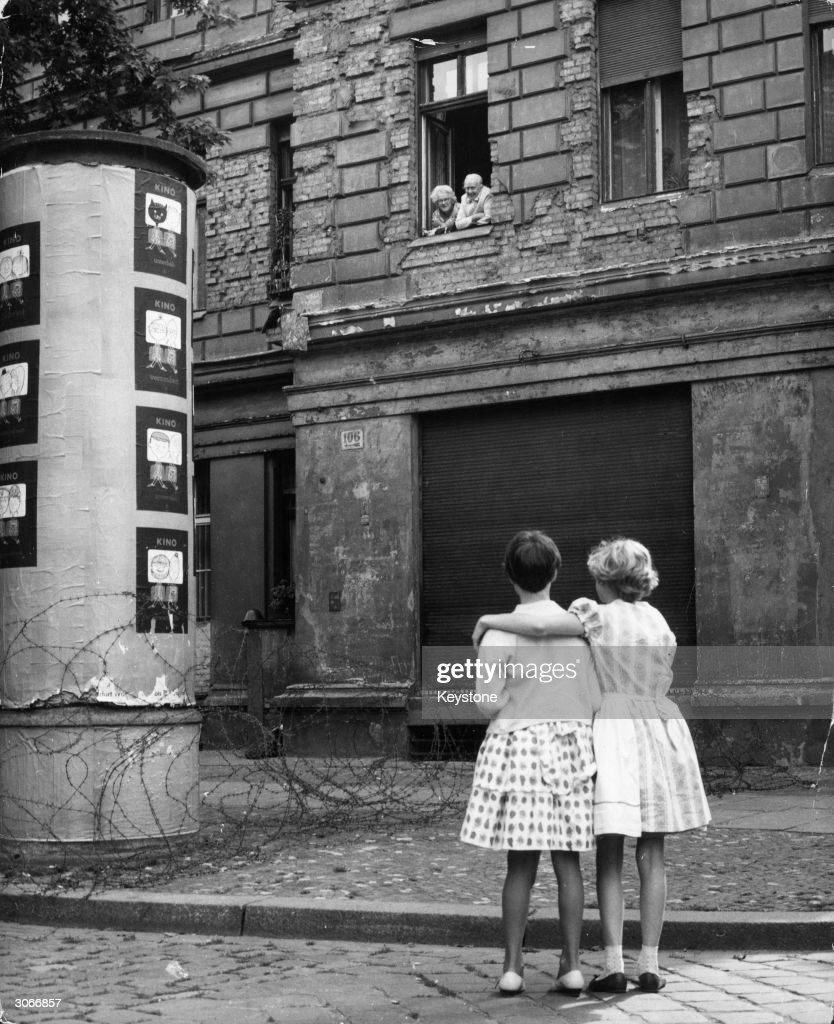 Two little girls in a West German street chat with their grandparents in the window of their home in the eastern zone, separated only by a barbed wire barricade.