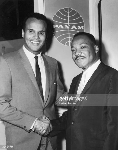 American singer and actor Harry Belafonte Jr shakes hands with American civil rights leader Rev Martin Luther King Jr at Kennedy International...