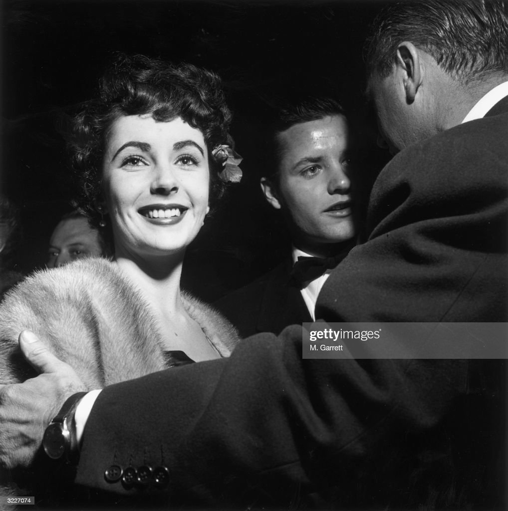 American actor Elizabeth Taylor smiling at the premiere of director Vincent Sherman's film 'The Hasty Heart', Hollywood, California. A man is placing his hand on Taylor's arm.