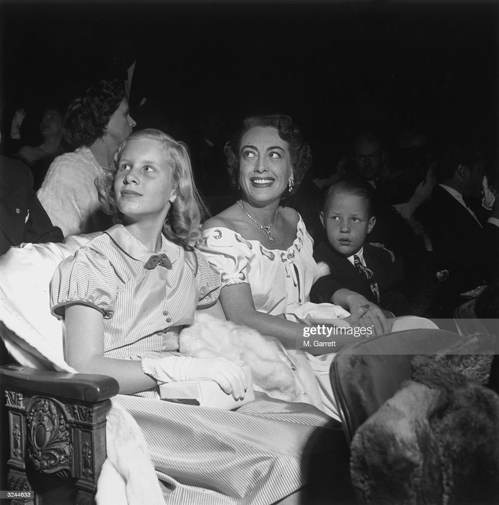 American actor Joan Crawford (1904 - 1977) smiles and holds hands with her children, Christina and Christopher, as she sits in a movie theater at the premiere of director Vincent Sherman's film, 'The Hasty Heart,' Hollywood, California.
