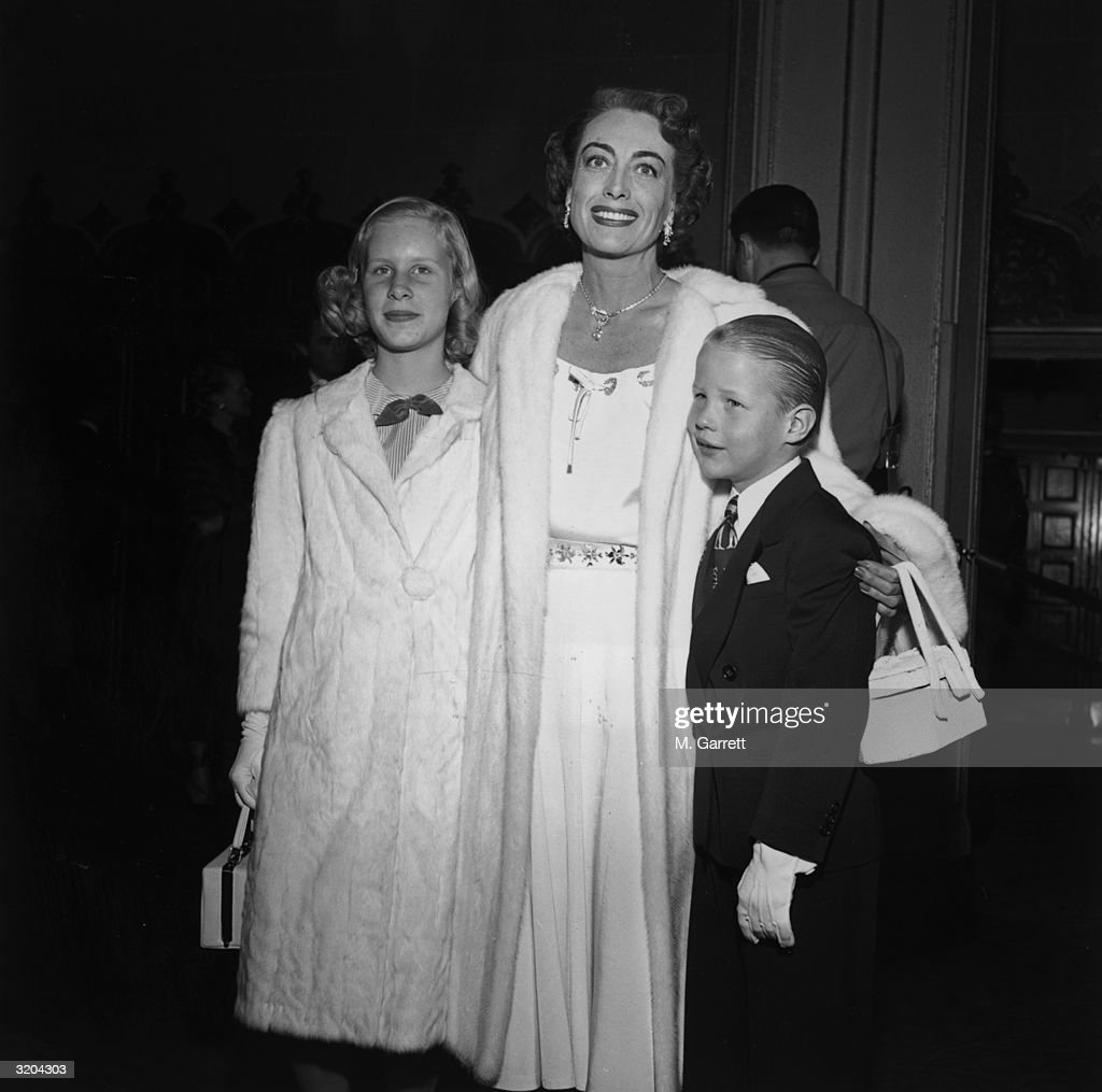 American actor <a gi-track='captionPersonalityLinkClicked' href=/galleries/search?phrase=Joan+Crawford&family=editorial&specificpeople=70017 ng-click='$event.stopPropagation()'>Joan Crawford</a> smiles as she poses with her daughter, Christina, and her son, Christopher, at the premiere of director Vincent Sherman's film, 'The Hasty Heart,' Hollywood, California. Crawford wears a white fur coat over a white dress.