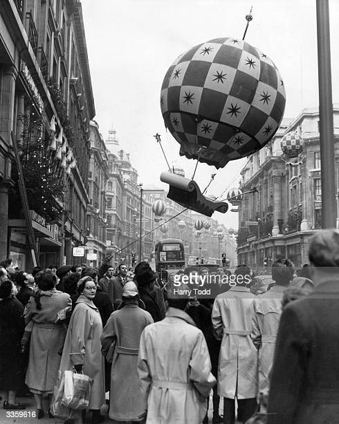 An inflatable decoration is floated back into place at Regent Street in London after it came loose during a gale