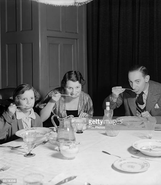 British actor and comedian Claude Hulbert eating dinner with his family at home