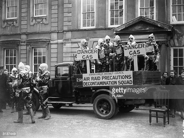 Wearing protective suits and gas masks members of the local Air Raid Precautions Decontamination Squad appeal for new volunteers outside the Council...