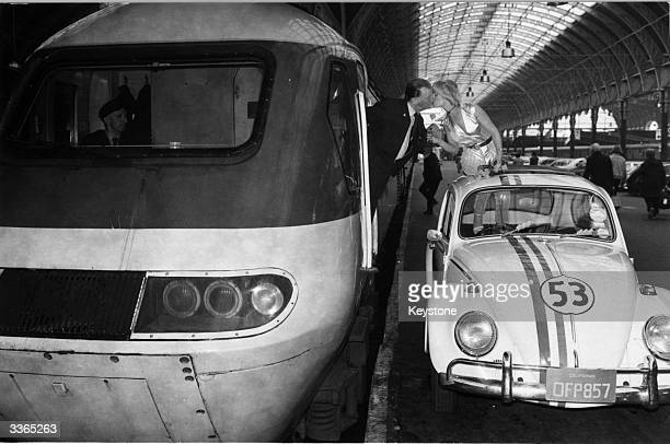 Actress Janey Love kisses train driver Tudor Lobb and hands him a rose from screen car 'Herbie' at Paddington Station on Valentine's Day part of the...