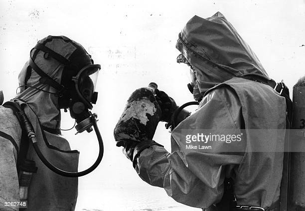 Fireman Steve Cansdale and school teacher Keith Terry check for oil and gas pollution on the beach at Ventnor on the Isle of Wight They are examining...