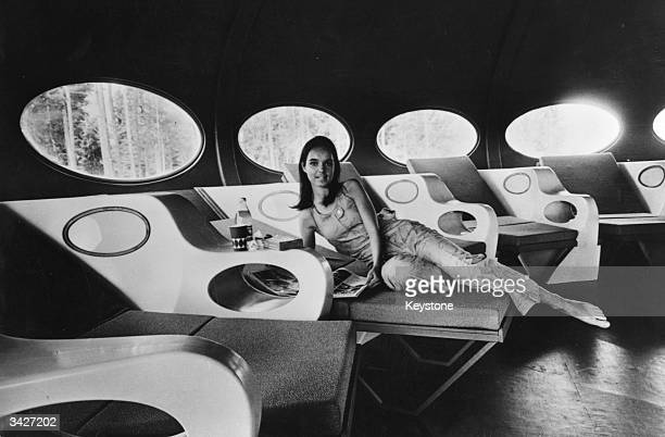 A woman reclines in the living room of a modern portable house called 'Futuro' which is manufactured by Oy Polykem AB of Helsinki The room is...