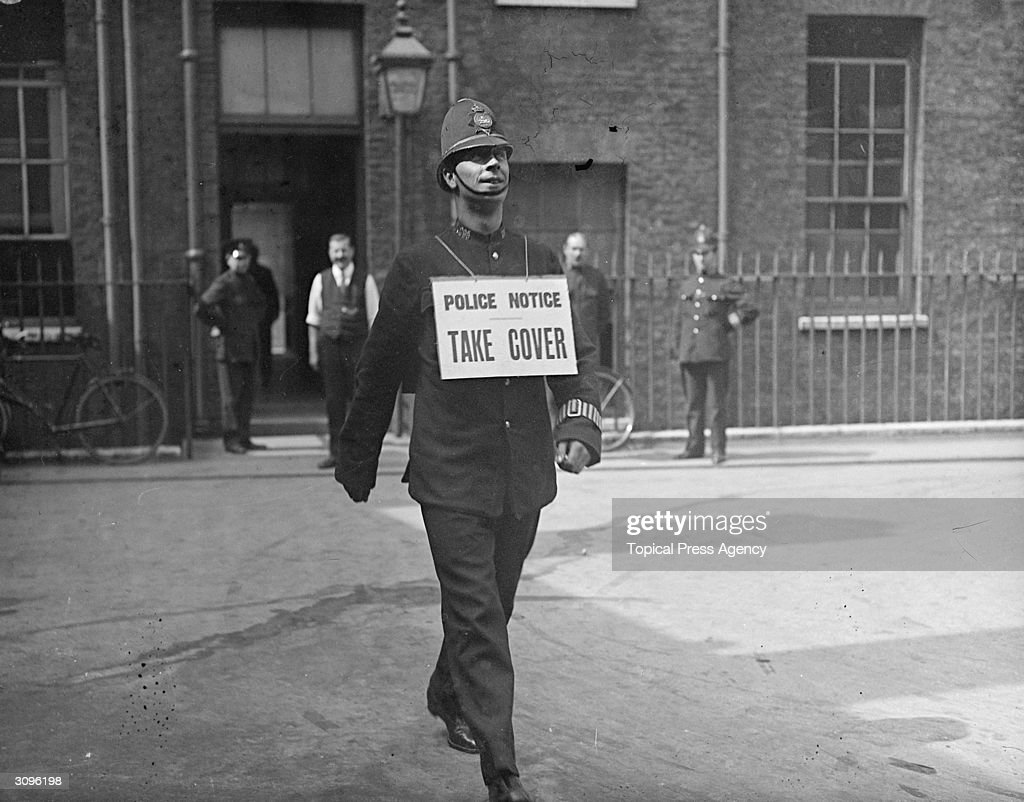 A policeman walking along during an air raid with a sign round his neck saying, 'Take Cover'.