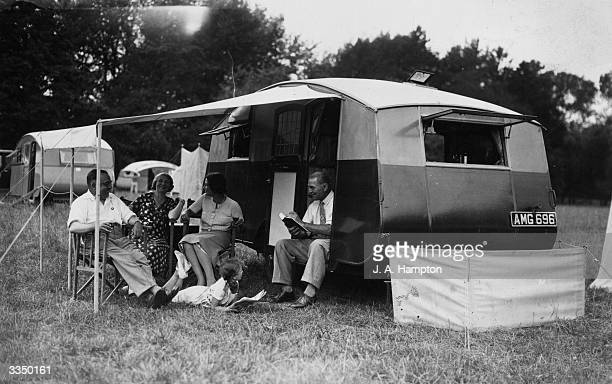 A family of campers relax outside their caravan at a gathering of the Camping Club of Great Britain and Ireland held at Hurley Farm Berkshire