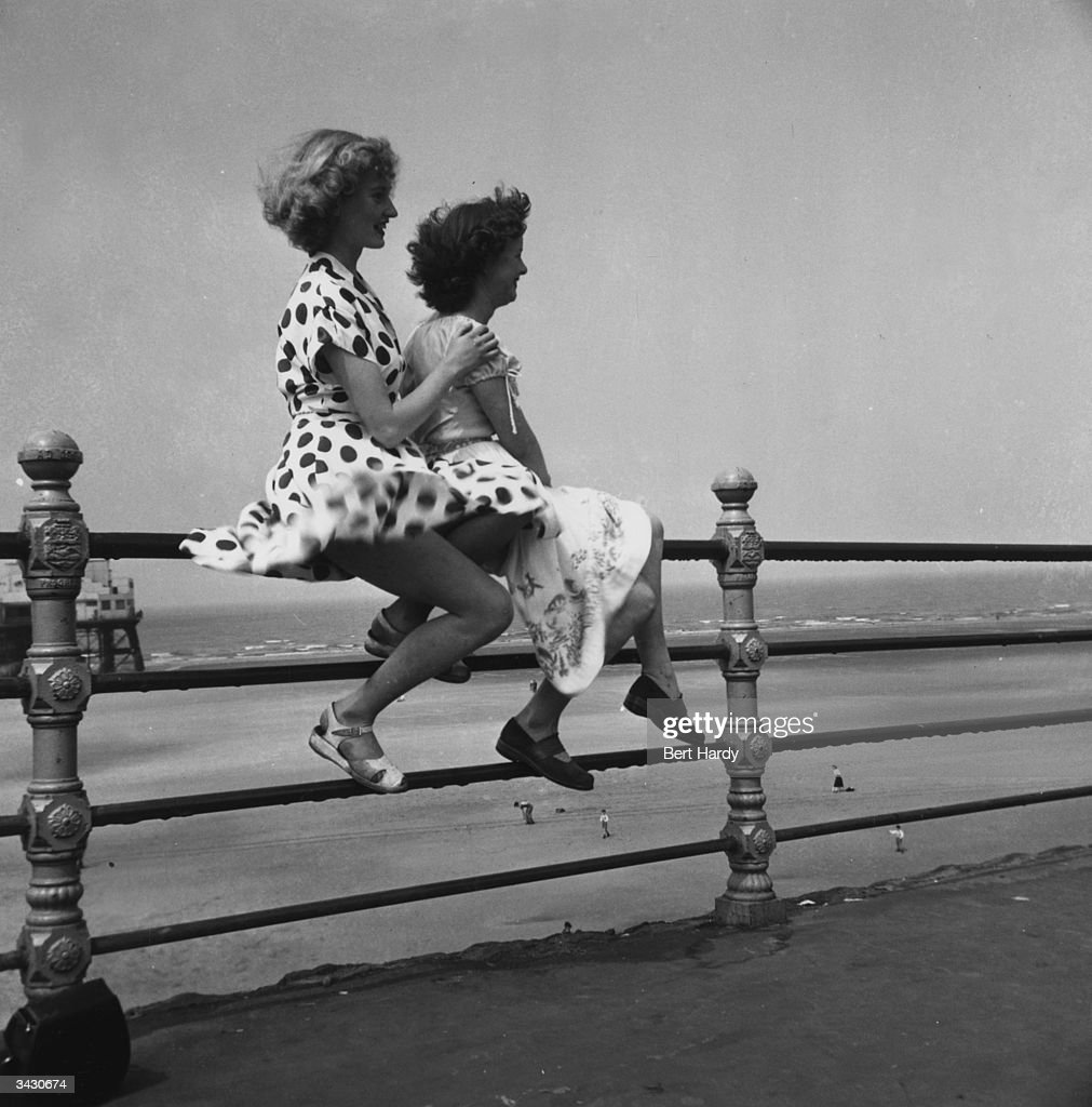 Two young women enjoy a summer day on Blackpool promenade as they sit on the railings with the wind billowing their skirts. They are former Tiller Girls Pat Wilson (left) of Bridgend, mid Glamorgan, and Wendy Clarke of Southall in London. Original Publication: Picture Post - 5358 - Bert Hardy's Box Camera - pub. 1951