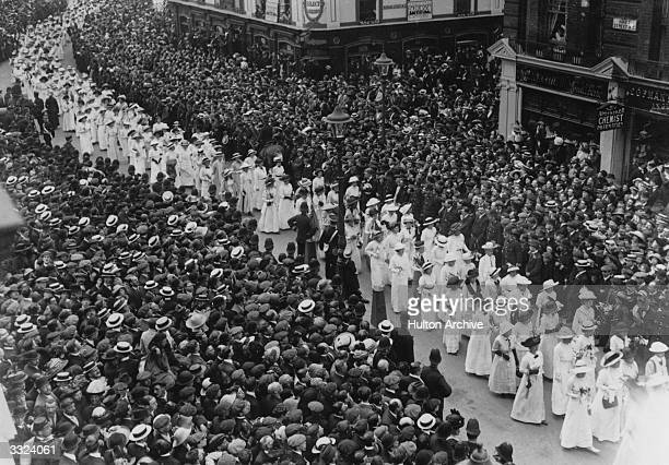 Crowds watch the funeral procession of English suffragette Emily Davison who died after being trampled by the king's horse at the Derby