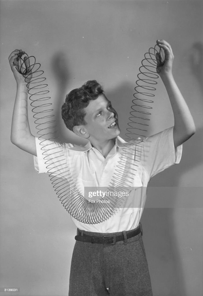 A boy holds up a 'slinky'. Made of a coil of wire which if straight would be 75 feet long a 'slinky' will 'climb' down a flight of stairs when coiled up and positioned correctly.